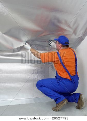 Construction worker affixing vapor insulation foil under thermally insulated attic surface