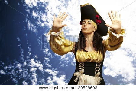 portrait of a pirate woman gesturing a stop symbol against a cloudy sky background