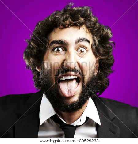 portrait of a young man joking and showing his tongue over a purple background