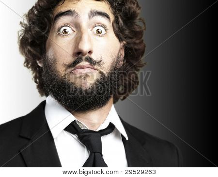 portrait of a young mans face afraid against a black background
