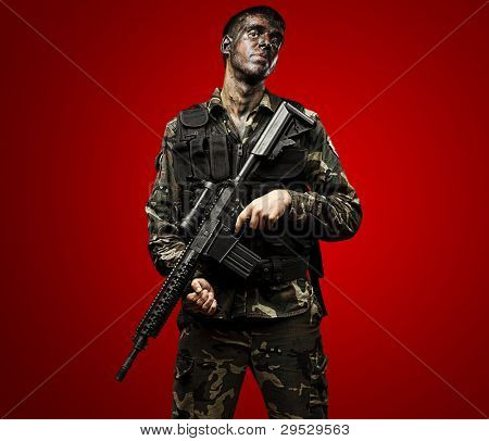 portrait of a young soldier painted with jungle camouflage holding a riffle over a red background