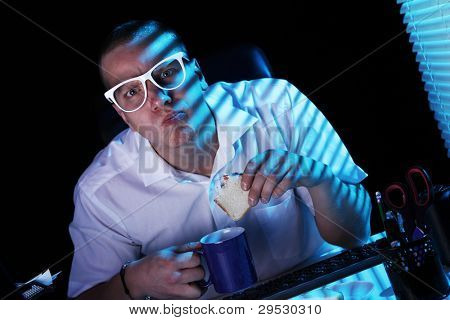 Funny nerd in glasses surfs internet at night time