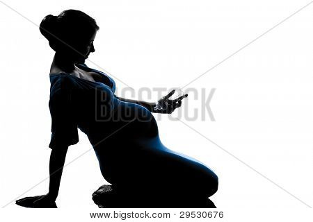 beautiful caucasian pregnant woman holding babby bottle in full length silhouette on studio isolated white background