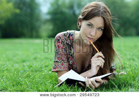 Die junge schöne Frau legt auf dem Gras im Park mit einem Tagebuch in Händen