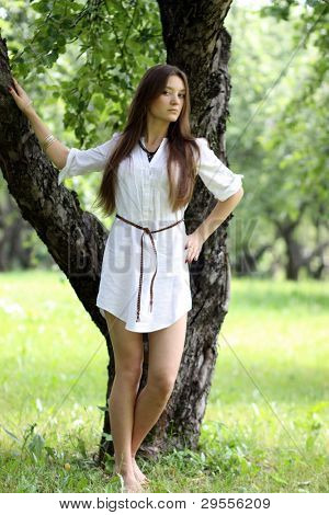 Pretty young beautiful girl standing near tree