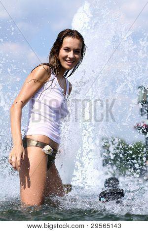 Joyful girl bathing in city fountain