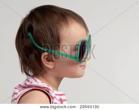 Cute child wearing glasses in a wrong way, side view