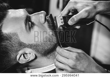 poster of Client During Beard Shaving In Barbershop. Young Handsome Barber And Attractive Bearded Man. Black A