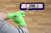 stock photo of dust mites  - cleaner is mopping a wooden parquet floor - JPG