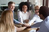 Happy Multi Ethnic Employees Stacking Hands Engaged In Team Building poster