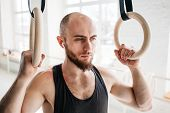 Male Bearded Athlete Resting And Holding Gymnastics Rings At Light Gym. Fit Man Relaxing On Gymnasti poster
