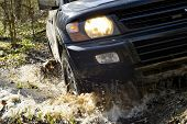 Suv Close-up Front Of It Passes Over Rough Terrain, Through A Puddle On A Dirty Road. Sharpness In T poster