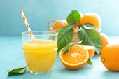 Orange Freshly Squeezed Juice In Glass And Fresh Fruits On A Blue Vivid Background, Top View poster