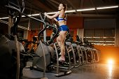Athletic Young Woman Exercise On Cardio Machine In The Gym. poster