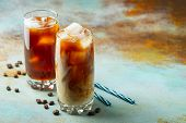 Ice Coffee In A Tall Glass With Cream Poured Over And Coffee Beans. Cold Summer Drink On A Blue Rust poster