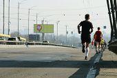 Strong Runners Running On City Bridge Road. Running On City Road. Marathon Running In The Morning Li poster