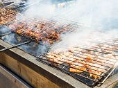 Grilled Meat Barbecue On Charcoal Stove With Full Of Smoke. Or Fire Charcoal In Stove For Cooking Fo poster