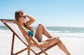 Smiling woman sunbathing on deck chair at beach. Attractive mature woman relaxing at seaside and loo poster