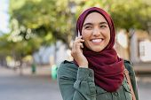 Beautiful and happy woman in hijab talking over mobile phone. Portrait of arabic woman in religious  poster