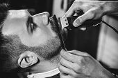 Client During Beard Shaving In Barbershop. Young Handsome Barber And Attractive Bearded Man. Black A poster