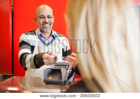 Mature man accepting credit card from young woman for payment of purchases