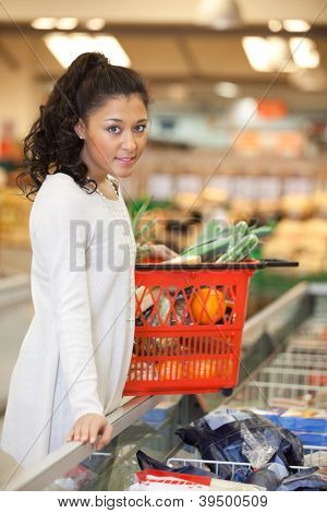 Portrait of young woman with shopping basket standing at checkout counter in supermarket