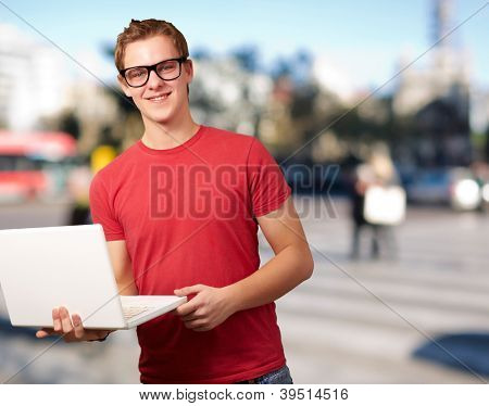 portrait of young student man holding laptop against a cityscape