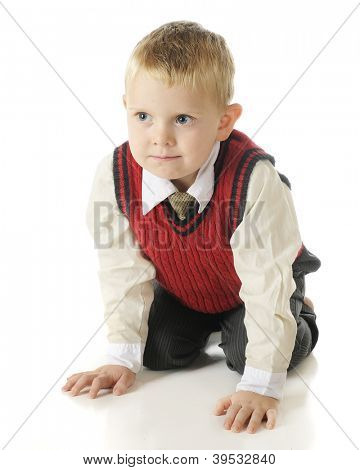 Front view of a handsome, kneeling preschooler dressed up in a red sweater vest and slacks.  On a white background.