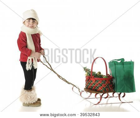 An adorable preschool girl dressed for winter.  She's pulling a sled holding a Christmas basket and green shopping bag.  On a white background.
