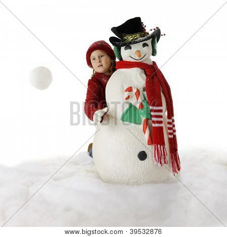 An elementary girl tosses a snowball from behind a Christmas snowman.  Motion blur on snowball.  On a white background.
