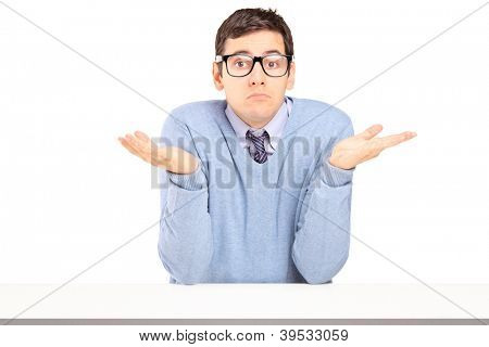 Doubtful young man sitting and gesturing with hands isolated on white background