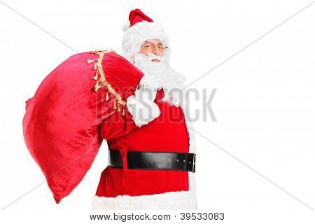 A Santa Claus walking with bag full of gifts og his back isolated on white background