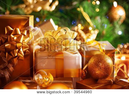 Image of luxury New Year gifts, different present boxes under Christmas tree in holiday eve, Christmastime celebration, home decorated with festive shiny balls, magic x-mas night