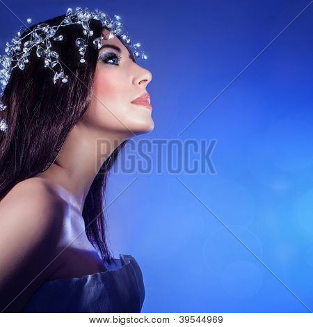 Picture of gorgeous woman isolated on blue background, closeup portrait of pretty brunet girl wearing festive jewelery, sexy female with stylish makeup and luxury accessories on head, New Year party