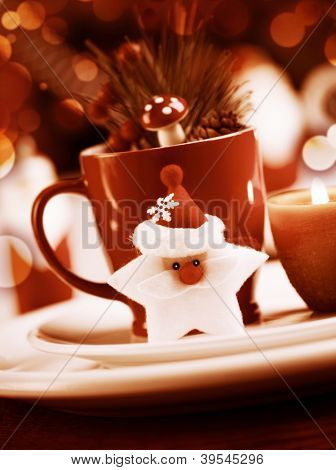 Grunge photo  of Christmastime utensil set, red tea cup standing on white plate and decorated with Santa Clause star toy, candle, fir cone and branch of Christmas tree, dark luxury xmas still life