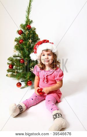 Baby With A Hat Of Santa Claus, A Red Ball And A Christmas Tree Isolated On White Background