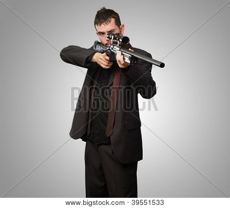 Young Man Aiming With Rifle against a grey background
