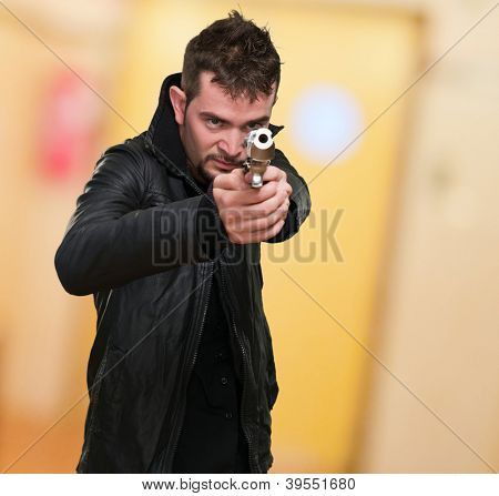 young man pointing with gun, indoor