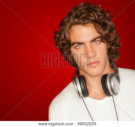 Handsome Man With Headphones Isolated On Red Background