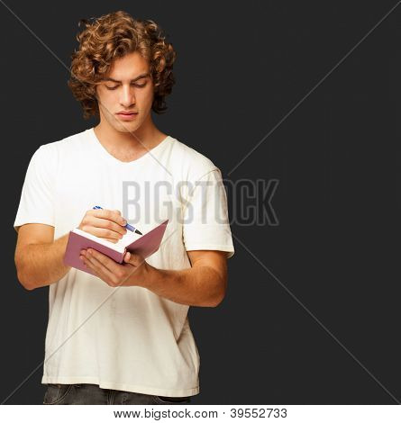A Young Man Writing On A Notebook Isolated On Black Background