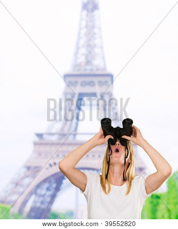 woman lookin up using binoculars in front of the eiffel tower