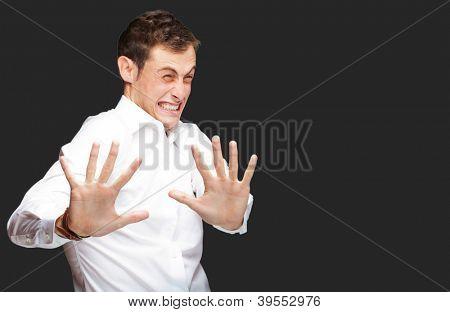 Ein junger Mann seine Hände heraus halten, In Angst auf schwarzem Hintergrund