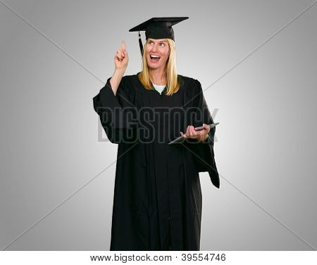Graduate Woman Holding Digital Tablet against a grey background