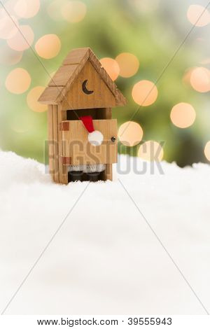 Santa in A Miniature Outhouse on Snow Over and Abstract Background.