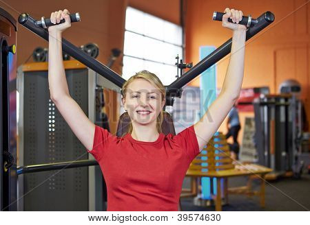 Smiling woman doing back exercises in fitness club on a shoulder press