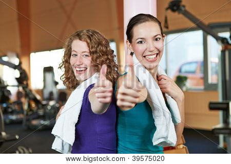 Two happy women in a fitness center holding their thumbs up