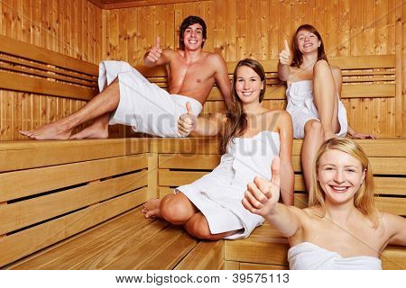 Four happy people in a sauna holding their thumbs up