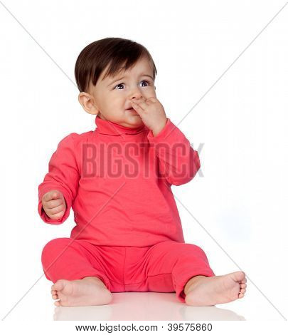 Scared baby girl with her hand in mouth sitting isolated on white background