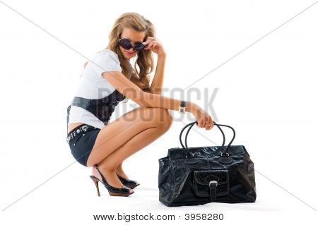 Attractive Girl With Sexy Dress And Big Fashion Bag Sitting On The Floor