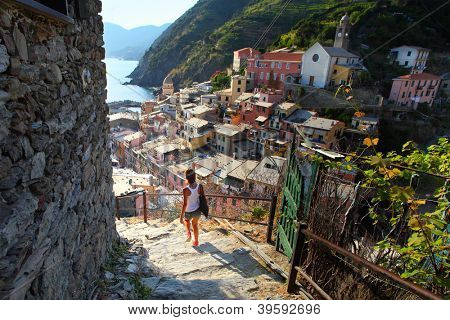 Young waman walking on stairs of small street of Vernazza town. Italy